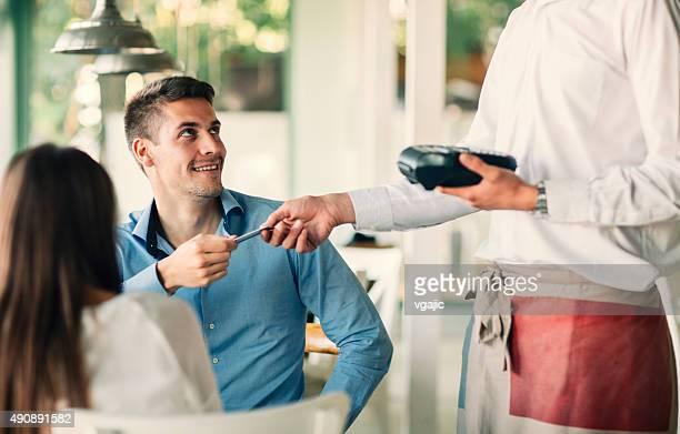 Hombre pagando con tarjeta de crédito, su almuerzo en el restaurante.