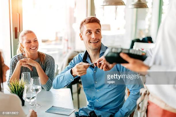 Homem pagar com cartão de crédito, o almoço em restaurante.