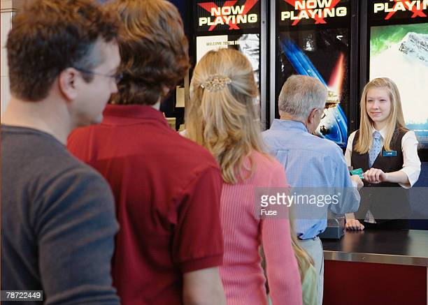 Man Paying Ticket Counter Person at Movie Theater