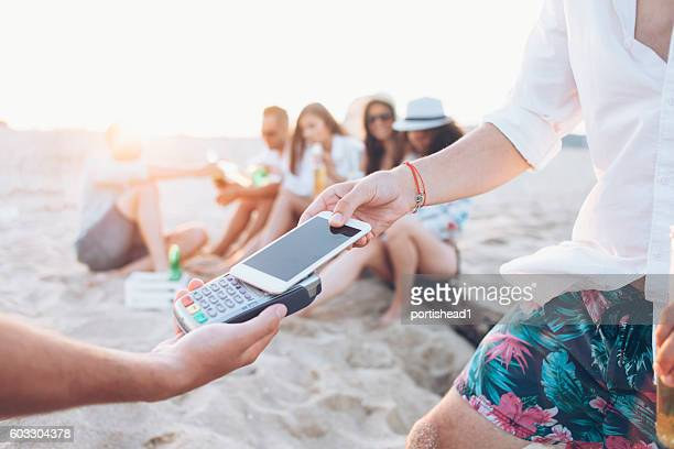 Man paying with smart phone on beach