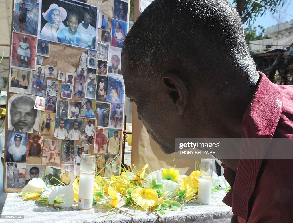 A man pays his respects at a makeshift memorial for victims of the January 12, 2010 Haiti earthquake near the destroyed Cathedral of Port-au-Prince on January 12, 2013. Three years after a massive earthquake ravaged Haiti, President Michel Martelly said the country was slowly rebuilding, despite the ongoing day-to-day misery of many survivors. An estimated 250,000 people were killed in the January 12, 2010 earthquake. Hundreds of thousands are still living rough in squalid makeshift camps, and they now face rampant crime, a cholera outbreak and the occasional hurricane.during memorial day in honor of the victims of the last quake of January 12 2013 in Haiti.People put photo of parent and friend victims of the quake. AFP PHOTO/Thony BELIZAIRE