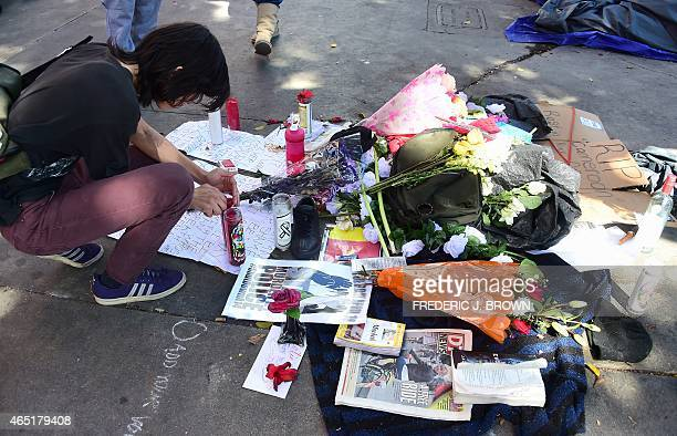 A man pays his respects beside an evergrowing makeshift memorial in Los Angeles California on March 3 2015 where a homeless man known as 'Africa' was...