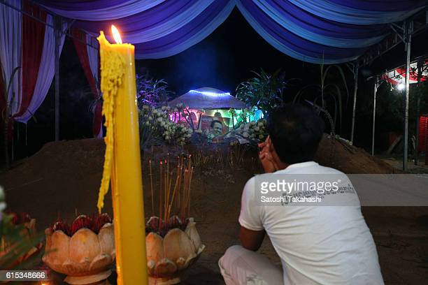 A man pays his respects to prominent political analyst Kem Ley in front of his grave during a funeral ceremony in Takeo province to mark 100 days...