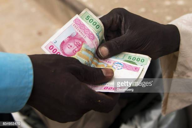A man pays with a vendor with Central African franc banknotes on a street in N'Djamena Chad on Wednesday Aug 16 2017 African Development Bank and...