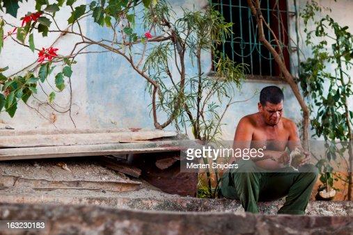 Man pealing coconut below flower bush : Stock Photo
