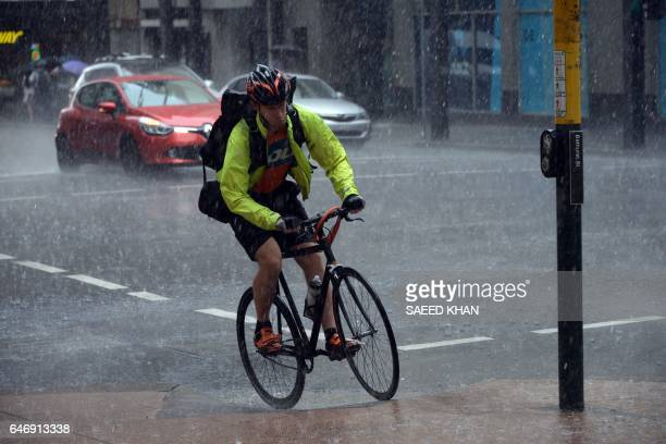 A man pedals his bike in heavy rain in the central business districk of Sydney on March 2 2017 / AFP PHOTO / SAEED KHAN