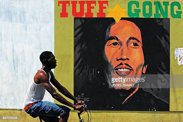 A man pedals past a mural of late musician Bob Marley in Kingston on February 8 2009 Marley who was born in 1945 and died in 1981 remains the most...