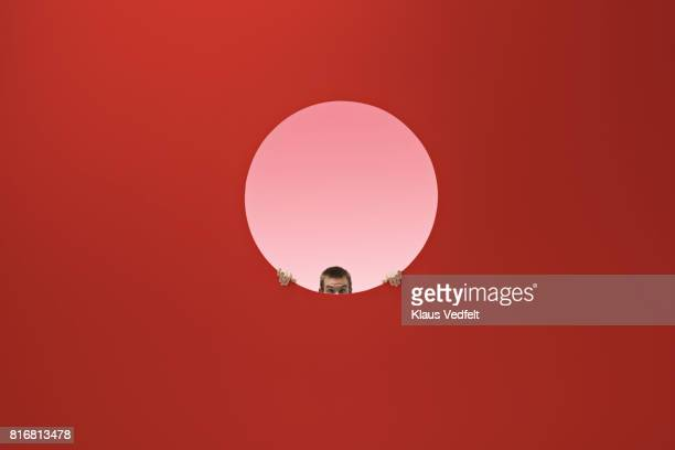 Man peeking out of round opening in coloured wall