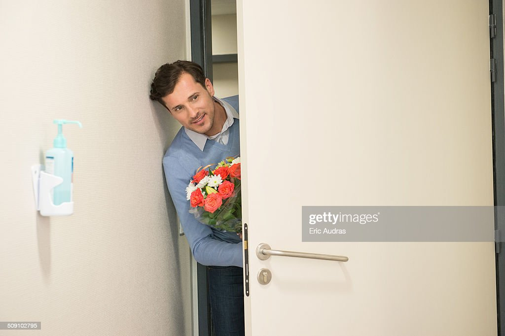 Man peeking through an open door with a bouquet of flowers in hospital room