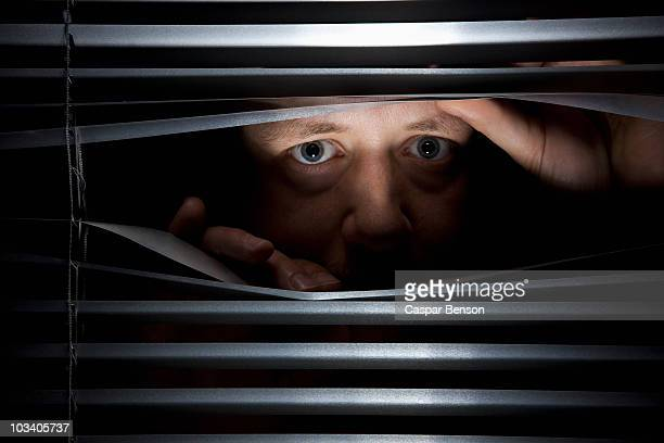 A man peeking through blinds