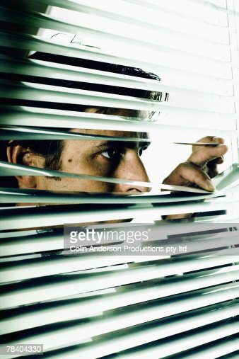 Man peeking through blinds : Stock Photo