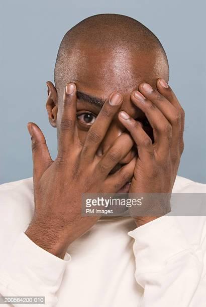 Man peeking through fingers, portrait, close-up