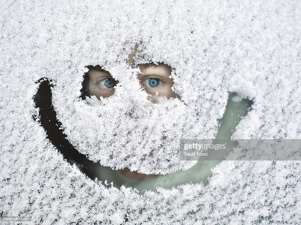 Man peeking through snow covered window : Stock Photo