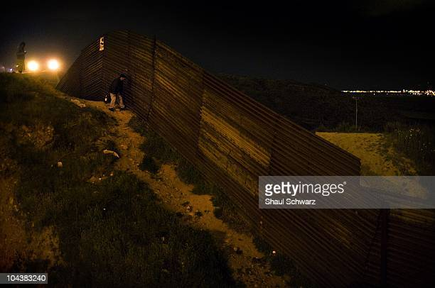 Man peeking through the fence towards the US border in an effort to study border patrol movement and paths to cross in Tijuana Mexico on the March 9...