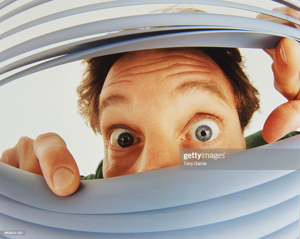 Man peeking through venetian blind, close-up : Stock Photo
