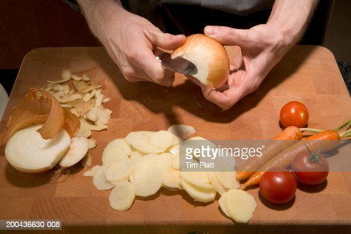 Man peeling onion above cutting board in kitchen, close-up : Stock Photo