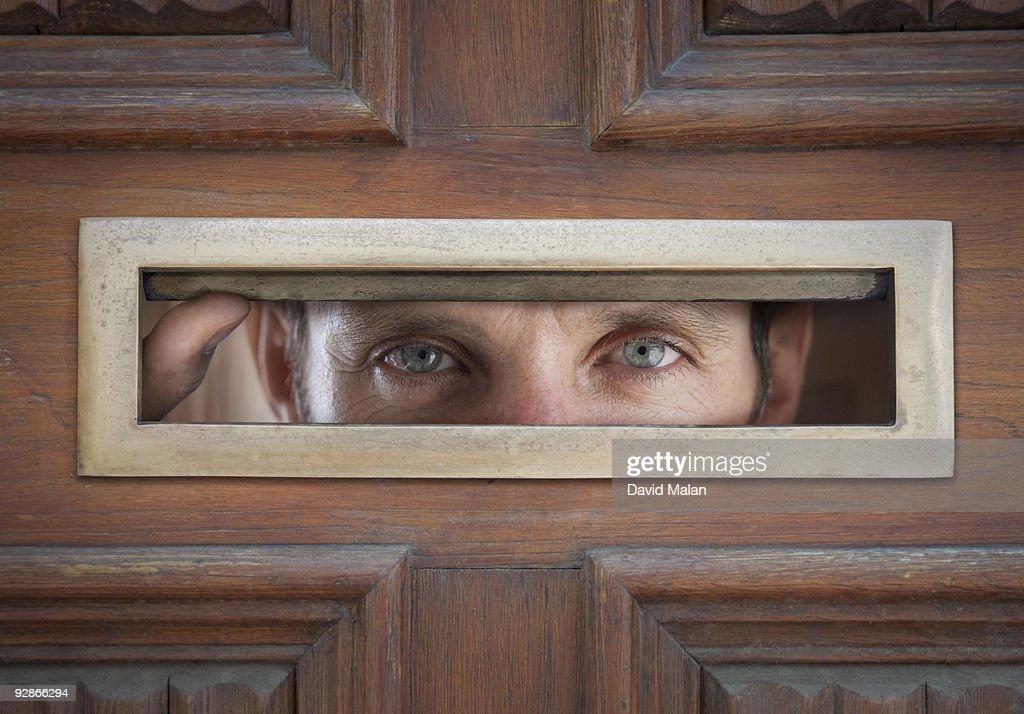 man peeping through letterbox in door : Stock Photo