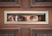 man peeping through letterbox in door