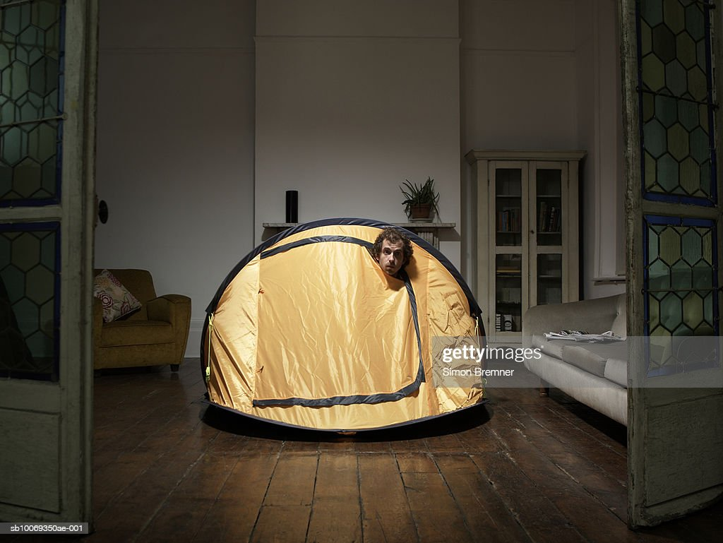 Man peering from tent in living room : Stock Photo