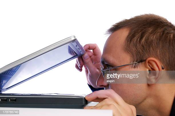 A man peering into an almost closed laptop