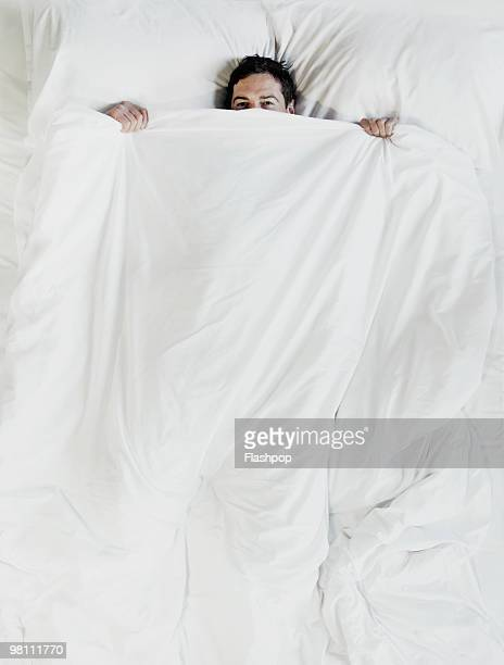 Man peering over the top of bed sheet