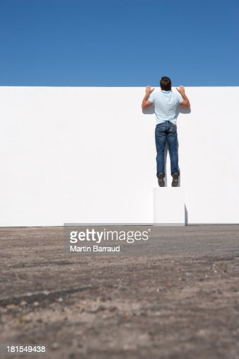 Man peering over wall outdoors with blue sky