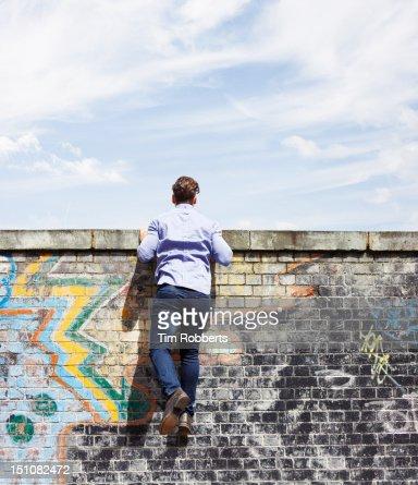 Man peering over wall.