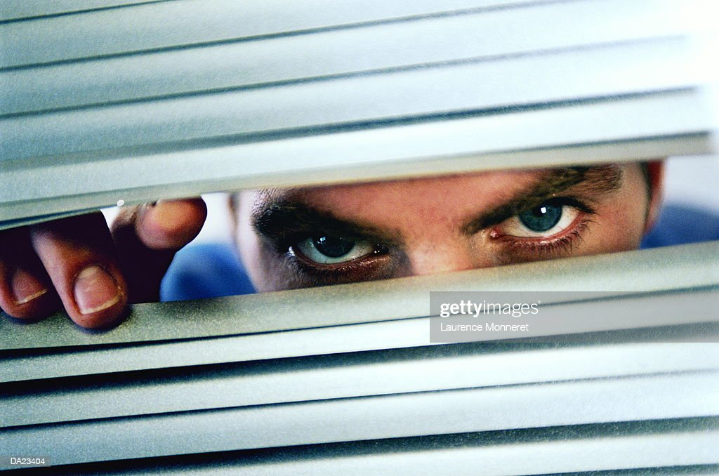 Man peering through blinds, close-up : Stock Photo