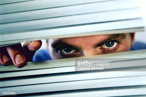 Man peering through blinds, close-up