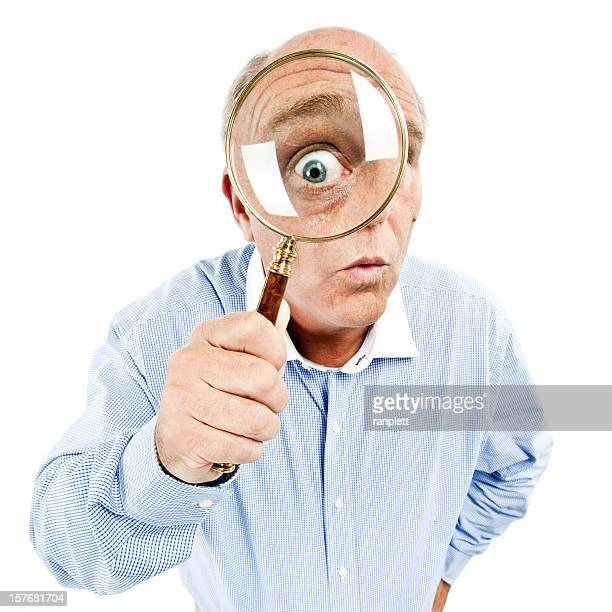 Man Peering through Magnifying Glass - Isolated