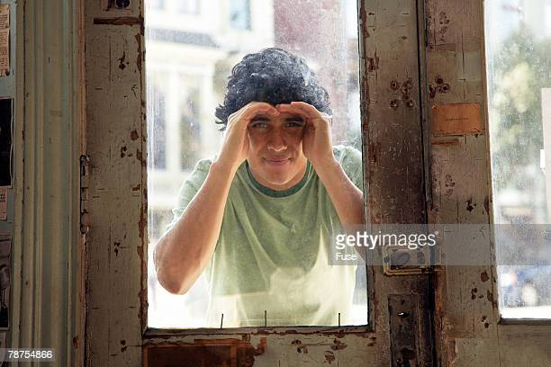 Man Peering Through Window of Closed Store