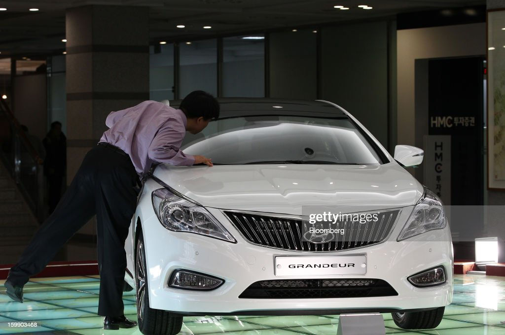 A man peers inside a Hyundai Motor Co. 5G Grandeur sedan on display in the showroom at the company's headquarters in Seoul, South Korea, on Tuesday, Jan. 22, 2013. Hyundai Motor Co. is scheduled to release fourth-quarter earnings on Jan. 24. Photographer: SeongJoon Cho/Bloomberg via Getty Images