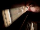 Man peers through window slats, doorway