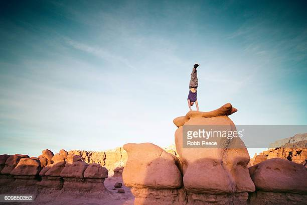 A man performing a handstand outdoors on rock formations in the desert