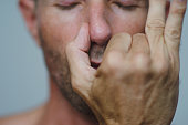 Man performing the yoga relaxation practice of alternate nostril breathing, holding a thumb to one side of the nose