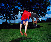 Man performing backflip in park (blurred motion)