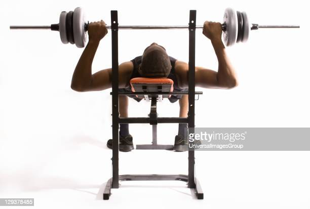 Man performing bench press exercise using specialist weight lifting equipment
