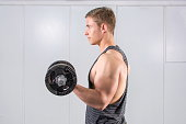 Man performing dumbbell curl at the gym. Biceps workout
