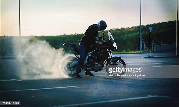 Man Performing Burnout On Motorcycle At Road