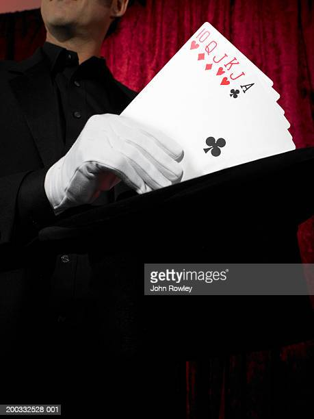Man performing card trick on stage, fanning cards, close-up