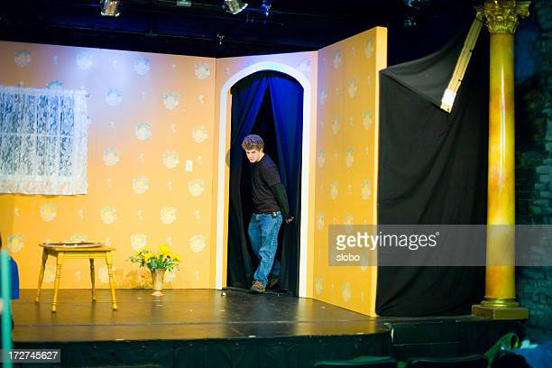 Man performing in theatrical production with yellow set
