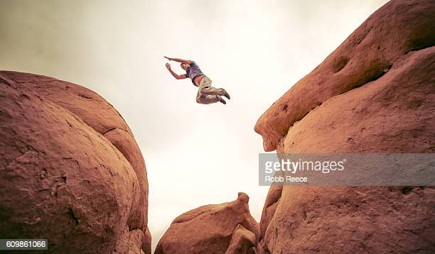 A man performing parkour outdoors on rock formations in the desert