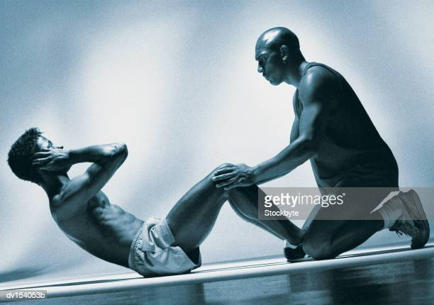 Man performing sit-ups with second man holding legs