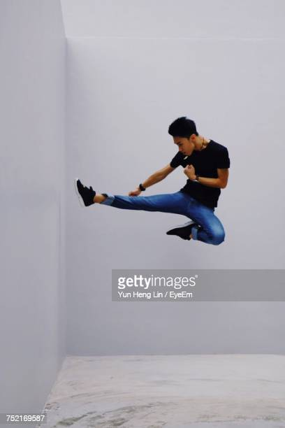 Man Performing Stunt Against White Wall