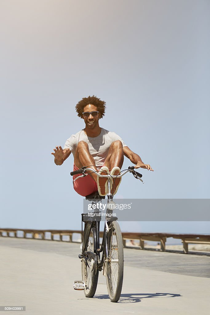 Man performing stunt on bicycle against blue sky