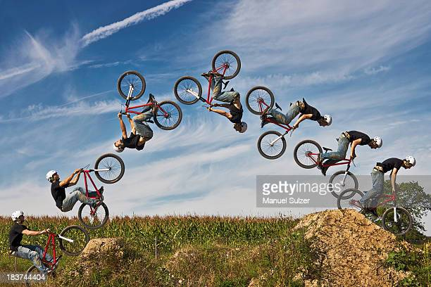 Man performing stunt on bmx bike, digital composite