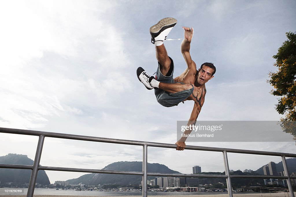 Man performs a parkour jump over a handrail. : Stock Photo