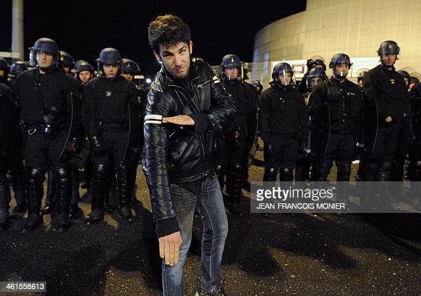 A man performs a 'quenelle' salute next to a line of French police officers after the performance of French controversial humorist Dieudonne M'bala...