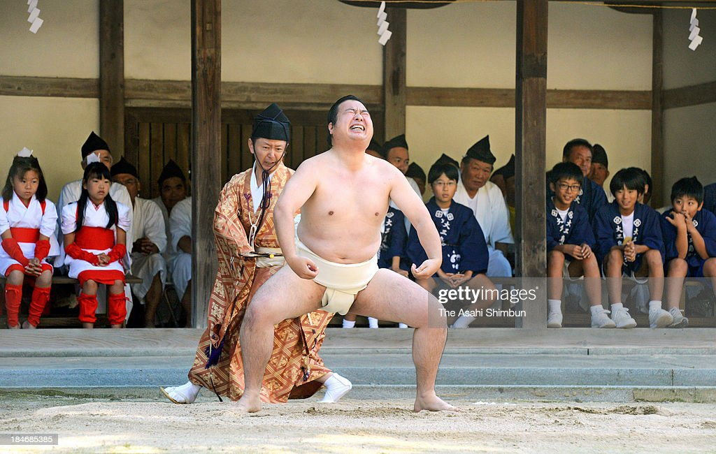 A man performs 'Hitori Zumo (or Lone Sumo)' to dedicate in appreciation for good rice harvest during the Nukiho-sai (Nukiho Festival) at Oyamazumi Shrine on October 13, 2013 in Imabari, Ehime, Japan. The sumo, a human being competes with the spirit of rice in 2-match sumo, has history back in 12th century and traditional the spirit win 2-1.