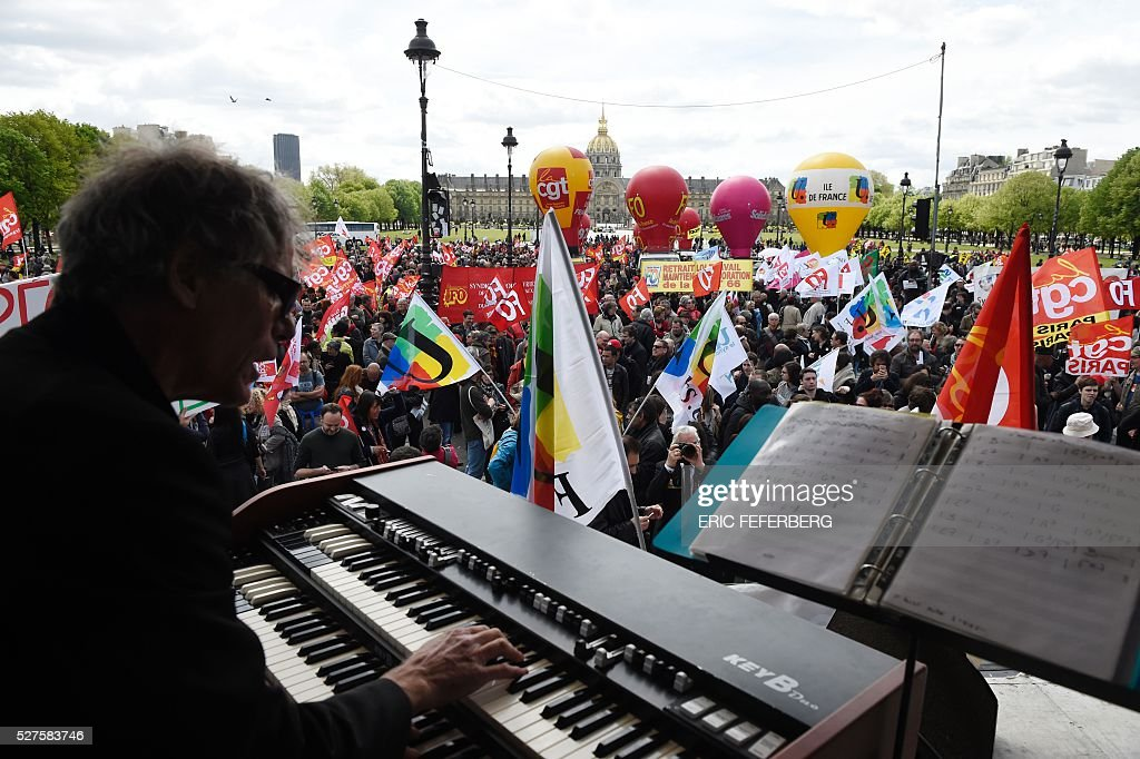 A man performs organ on stage as people gather during a protest against the government's planned labour law reforms on May 3, 2016, in Paris as French lawmakers begin to examine the contested labour reform bill at the Parliament. Unions fear it will erode the cherished rights of workers on full-time contracts, while student organisations -- who have been at the forefront of the protests -- believe it will fail to create 'real' jobs for young people.